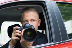 Homme photographiant avec l'appareil-photo de slr de la voiture Images stock