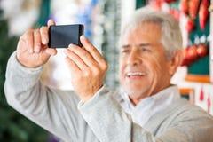 Homme photographiant dans le magasin de Noël Photos stock