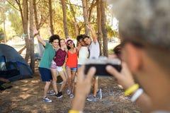 Homme photographiant des amis au terrain de camping Photos libres de droits