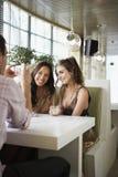 Homme photographiant des amis en café Image stock
