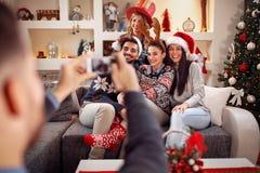 Homme photographiant des amis par le téléphone pour Noël Photos libres de droits