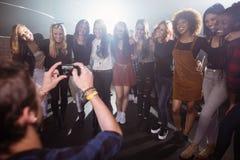 Homme photographiant les amis féminins heureux à la boîte de nuit Photo libre de droits