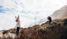 Homme photographiant son amie pendant des vacances Photos stock
