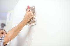Homme plâtrant un mur blanc Photos libres de droits