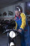 Homme plaçant une motocyclette Images libres de droits