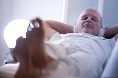 Homme plein d'assurance détendant sur un sofa Images stock