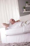 Homme plein d'assurance détendant sur un sofa Photographie stock
