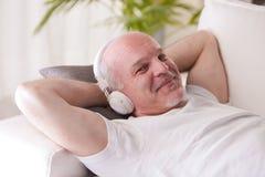 Homme plein d'assurance détendant sur un sofa Image libre de droits