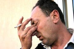 Homme pleurant avec la cigarette Photographie stock libre de droits