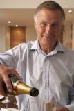 Homme pleuvant à torrents une glace de Champagne Images libres de droits
