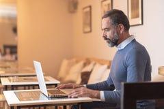 Homme plus âgé à l'aide d'un ordinateur portable dans un café photo libre de droits