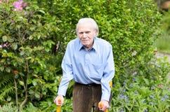 Homme plus âgé à l'aide des béquilles d'avant-bras pour marcher Image libre de droits