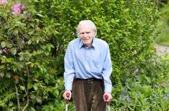 Homme plus âgé à l'aide des béquilles d'avant-bras pour marcher Images stock