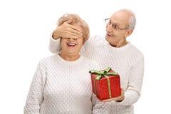 Homme plus âgé étonnant une femme agée avec un cadeau Photographie stock