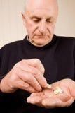 Homme plus âgé aîné prenant une tablette ou une pillule Photos libres de droits