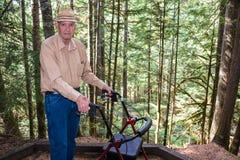 Homme plus âgé actif avec le marcheur dans la forêt Images stock
