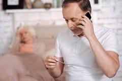 Homme plus âgé appelle l'urgence tout en vérifiant le thermomètre Photographie stock libre de droits