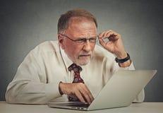 Homme plus âgé avec des verres confus avec le logiciel d'ordinateur portable Photos stock