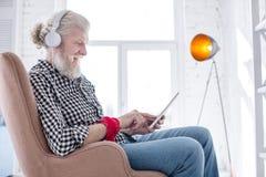 Homme plus âgé avec du charme écoutant la musique et la causerie Photos stock