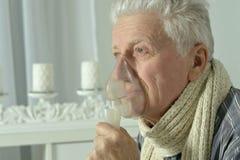 Homme plus âgé avec l'inhalation de grippe Photographie stock
