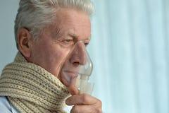 Homme plus âgé avec l'inhalation de grippe Photographie stock libre de droits