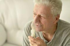 Homme plus âgé avec l'inhalation de grippe Image stock
