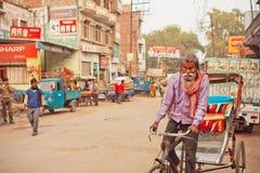 Homme plus âgé avec la barbe blanche conduisant en bicyclette avec le chariot Photos stock