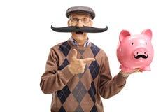 Homme plus âgé avec la fausse moustache se dirigeant à une tirelire Photo libre de droits