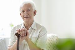 Homme plus âgé avec le bâton de marche en bois dans la maison de soins image libre de droits