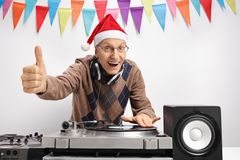 Homme plus âgé avec le chapeau de Noël faisant le pouce vers le haut du signe Images libres de droits