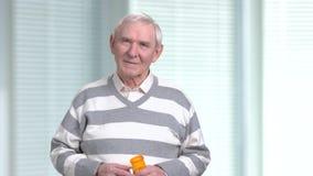 Homme plus âgé avec le médicament, fond brouillé banque de vidéos