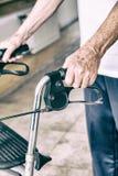 Homme plus âgé avec le marcheur se déplaçant à l'hôpital, détail sur des mains image stock