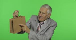 Homme plus âgé avec le sac à provisions Regarde dans la caméra et étire le cadeau banque de vidéos