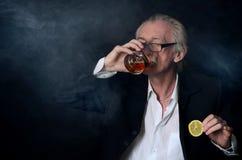 Homme plus âgé avec un verre de whiskey sur le fond noir Photo stock
