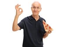 Homme plus âgé ayant une tranche de pizza Photos libres de droits