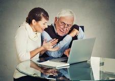 Homme plus âgé confus de enseignement de femme comment utiliser l'ordinateur portable Image libre de droits