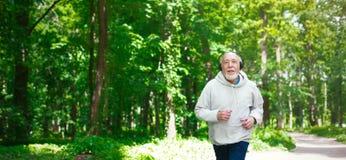 Homme plus âgé courant dans la forêt verte, l'espace de copie Photo libre de droits