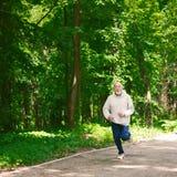 Homme plus âgé courant dans la forêt verte, l'espace de copie Images libres de droits