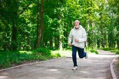 Homme plus âgé courant dans la forêt verte, l'espace de copie Images stock