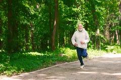 Homme plus âgé courant dans la forêt verte, l'espace de copie Photographie stock