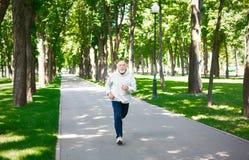 Homme plus âgé courant en parc vert, l'espace de copie Images stock