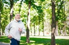 Homme plus âgé courant en parc vert, l'espace de copie Photographie stock