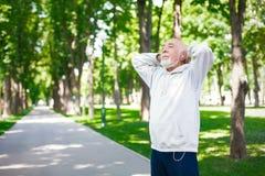 Homme plus âgé courant en parc vert, l'espace de copie Photos stock