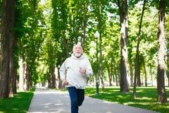 Homme plus âgé courant en parc vert, l'espace de copie Photographie stock libre de droits
