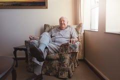Homme plus âgé décontracté s'asseyant sur une chaise de bras Images stock