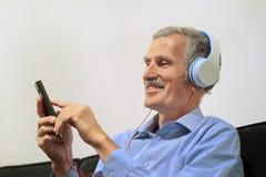 Homme plus âgé dans des écouteurs écoutant la musique photo stock