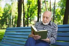 Homme plus âgé dans la lecture occasionnelle dehors Images libres de droits