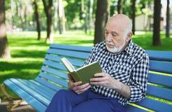 Homme plus âgé dans la lecture occasionnelle dehors Image libre de droits