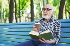 Homme plus âgé dans la lecture occasionnelle dehors Photo stock