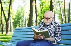 Homme plus âgé dans la lecture occasionnelle dehors Photographie stock libre de droits